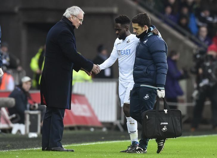 Football Soccer Britain - Swansea City v Leicester City - Premier League - Liberty Stadium - 12/2/17 Swansea City's Nathan Dyer receives medical attention after sustaining an injury while Leicester City manager Claudio Ranieri looks on Reuters / Rebecca Naden Livepic