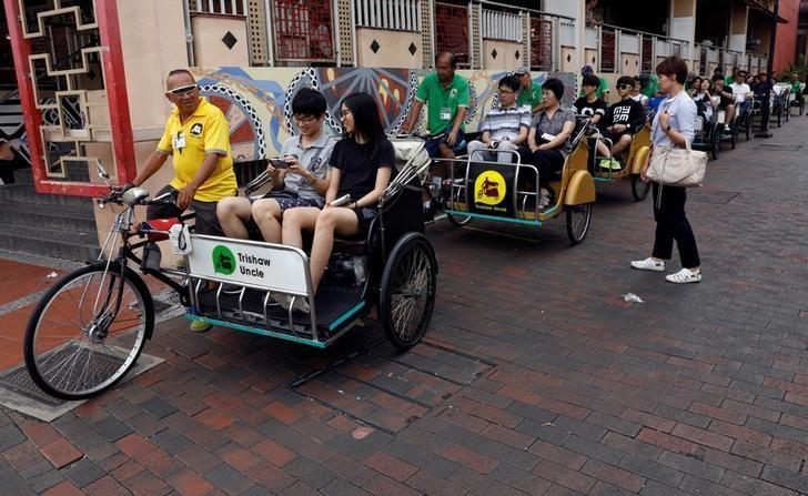 Tourists ride trishaws in Singapore January 5, 2017. REUTERS/Edgar Su/Files