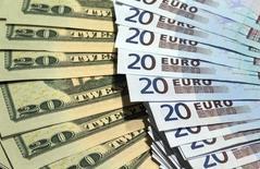 Банкноты евро и доллара США в пункте обмена валюты в Париже. 28 октября 2014 года.Доллар расширил потери во вторник после того, как советник президента США Дональда Трампа по национальной безопасности Майкл Флинн подал в отставку. REUTERS/Philippe Wojazer