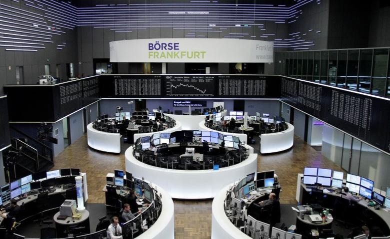 Traders work at their desks in front of the German share price index, DAX board, at the stock exchange in Frankfurt, Germany, February 8, 2017. REUTERS/Staff/Remote