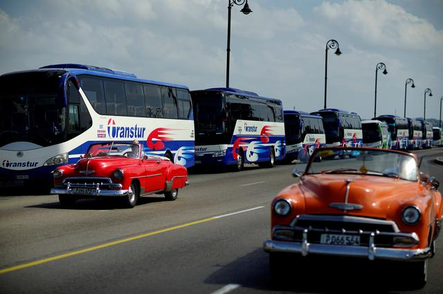 Vintage cars pass by a fleet of Chinese-made Yutong buses parked at the sea front Malecon in Havana, Cuba, February 10, 2017. REUTERS/Alexandre Meneghini