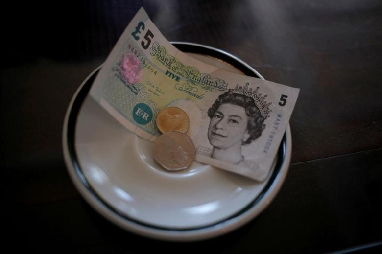 An English five pound note and coins are seen at a restaurant in the British overseas territory of Gibraltar, July 21, 2016. REUTERS/Jon Nazca/FILE PHOTO