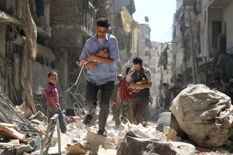 Syrian men carrying babies make their way through the rubble of destroyed buildings following a reported airstrike on the rebel-held Salihin neighborhood of Aleppo on 11 September 2016.  Ameer Alhalbi, Agence France-Presse/Courtesy of World Press Photo Foundation/Handout via REUTERS