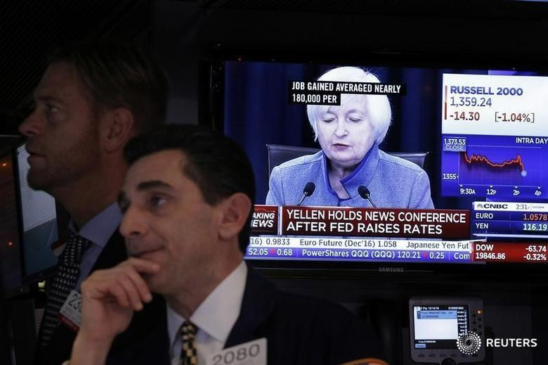 FILE PHOTO - Traders works on the floor of the New York Stock Exchange (NYSE) as a television screen displays coverage of U.S. Federal Reserve Chairman Janet Yellen, in New York, U.S., December 14, 2016.  REUTERS/Lucas Jackson