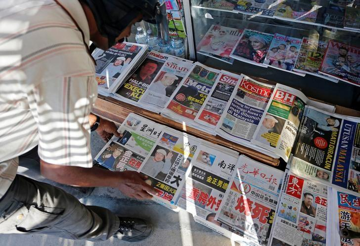 A newspaper vendor arranges newspapers showing front pages with images of Kim Jong Nam, at a news-stand outside Kuala Lumpur, Malaysia February 15, 2017. REUTERS/Lai Seng Sin