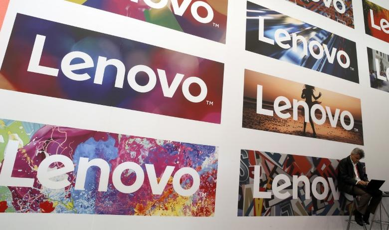 A man uses his laptop next to Lenovo's logos during the Mobile World Congress in Barcelona, Spain February 25, 2016. REUTERS/Albert Gea