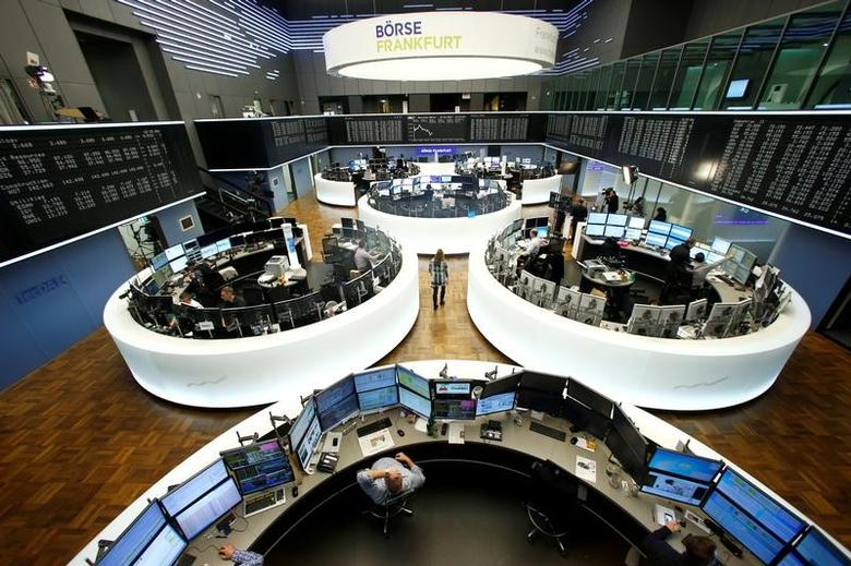 Traders work at their desks in front of the German share price index, DAX board, at the stock exchange in Frankfurt, Germany, February 15, 2017. REUTERS/Ralph Orlowski