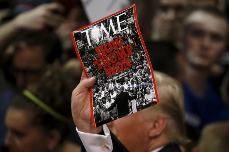 U.S. Republican presidential candidate Donald Trump holds up a Time Magazine cover following a campaign rally in Syracuse, New York April 16, 2016. REUTERS/Carlo Allegri