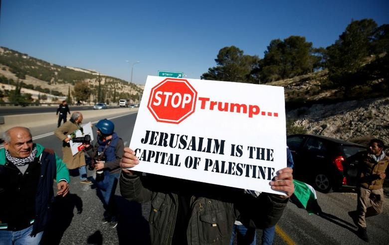 FILE PHOTO - A Palestinian demonstrator holds placard during a protest against a promise by U.S. President-elect Donald Trump to re-locate U.S. embassy to Jerusalem, in the West Bank near Jewish settlement of Maale Adumim, January 20, 2017. REUTERS/Mohamad Torokman/File Photo