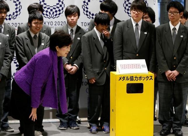 2月16日、東京都は不要になった携帯電話などに含まれる金属から2020年東京五輪のメダルを製造するキャンペーンを開始し、都庁に回収箱が設置された。写真左は式典に出席した小池百合子・東京都知事(2017年 ロイター/Issei Kato)