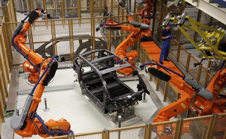 A worker makes technical measurements with robots on the carbon chassis at the serial production BMW i3 electric car in the BMW factory in Leipzig  on September 18, 2013.  REUTERS/Fabrizio Bensch