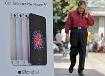 En la imagen, un hombre habla por teléfono mientras pasa al lado de un anuncio del iPhone SE de Apple en Nueva Delhi, India, el 25 de abril de 2016. Apple Inc comenzará a fabricar sus modelos de menor precio iPhone SE en la planta de un productor contratado en Bangalore, la ciudad del sur de India que acoge a varias empresas de tecnología, dijo el viernes una fuente de la industria con conocimiento directo del asunto. REUTERS/Anindito Mukherjee