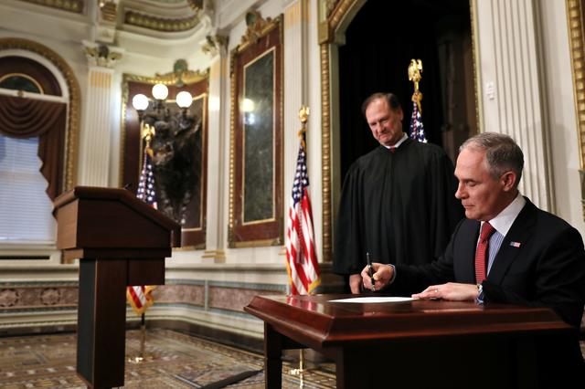 Director of Environmental Protection Agency Scott Pruitt signs a document after his swearing-in ceremony, accompanied by Justice Samuel Alito (L) at the Executive Office in Washington, U.S., February 17, 2017. REUTERS/Carlos Barria