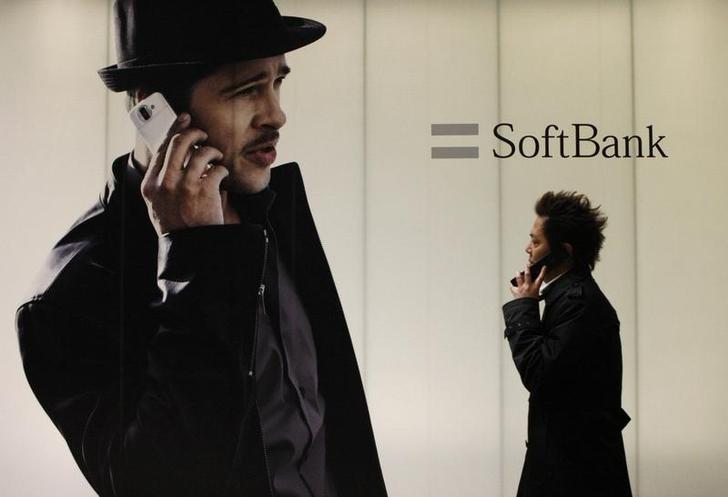 A man using a mobile phone walks past an advertisement board of Softbank Corp in Tokyo February 5, 2009. REUTERS/Toru Hanai/Files