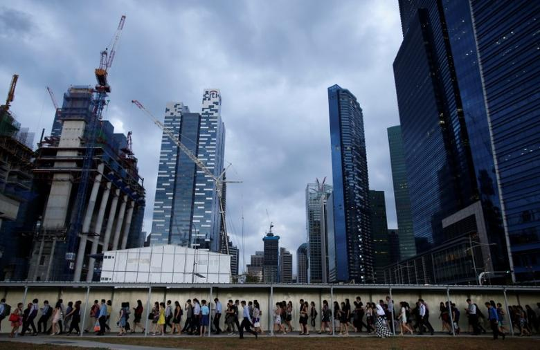 Office workers walk to the train station during evening rush hour in the financial district of Singapore March 9, 2015. REUTERS/Edgar Su/File Photo