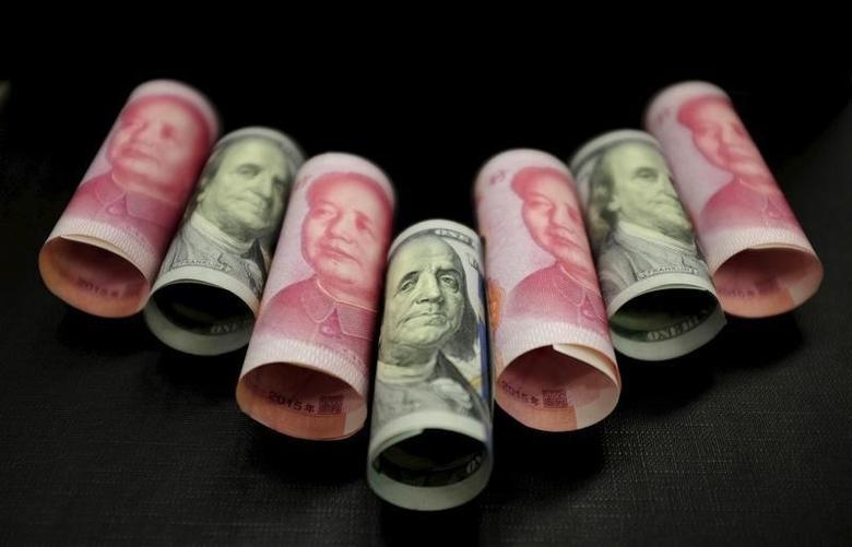 图为百元面值的人民币纸币及美元现钞。REUTERS/Jason Lee