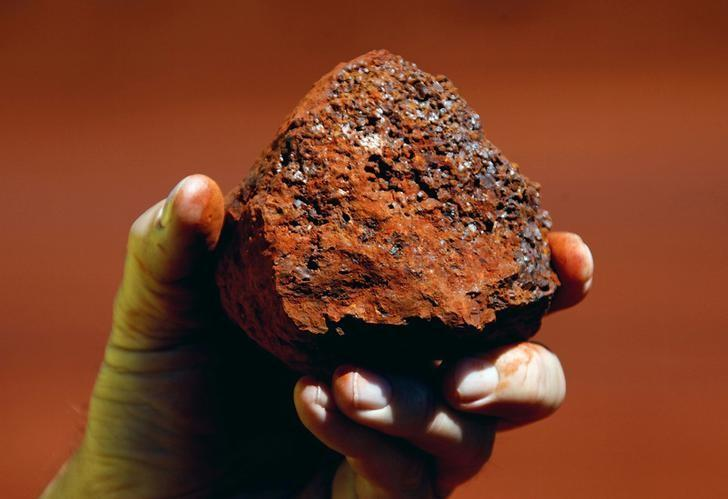 A miner holds a lump of iron ore at a mine located in the Pilbara region of Western Australia, December 2, 2013.   REUTERS/David Gray/File photo - RTX2PF9Q