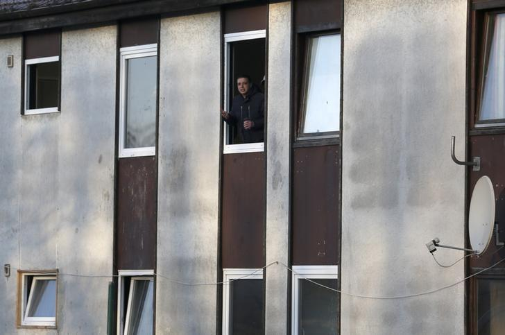 A man watches from a window of an accommodation center for asylum seekers in Recklinghausen, north of Cologne, Germany January 22, 2016.  REUTERS/Ina Fassbender