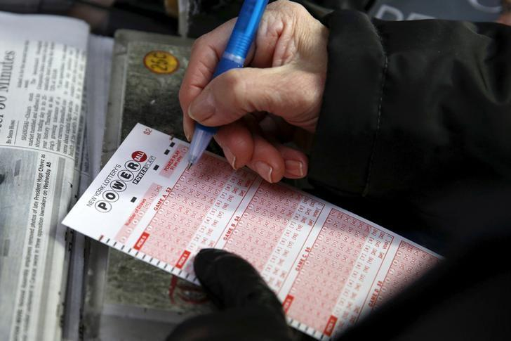 File Photo: A woman fills out a ticket for the $700 million Powerball lottery draw at Times Square in the Manhattan borough of New York January 7, 2016. REUTERS/Shannon Stapleton/File Photo