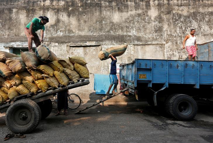 A labourer loads a sack of red chilies into a supply truck at a wholesale market in Kolkata, January 16, 2017. REUTERS/Rupak De Chowdhuri/Files