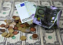 Dollar banknotes and Euro banknote and coins are seen in front of destroyed Euro saving money box in this picture illustration taken February 16, 2017. REUTERS/Dado Ruvic/Illustration