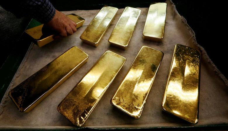 FILE PHOTO: An employee places ingots of 99.99 percent pure gold on a cart at the Krastsvetmet non-ferrous metals plant, one of the world's largest producers in the precious metals industry, in the Siberian city of Krasnoyarsk, Russia October 24, 2016. REUTERS/Ilya Naymushin/File Photo