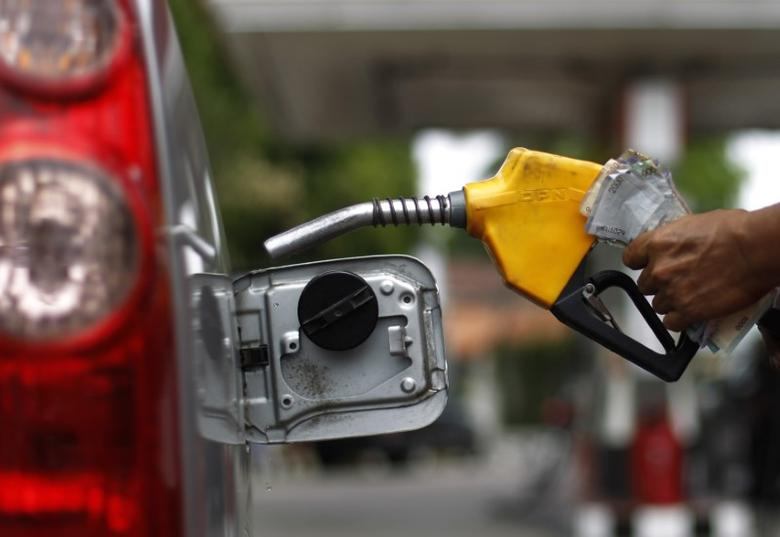 FILE PHOTO - A worker fills a tank with subsidized fuel at a fuel station in Jakarta April 18, 2013. REUTERS/Beawiharta