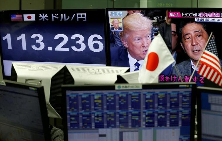 FILE PHOTO: A TV monitor showing U.S. President Donald Trump and Japanese Prime Minister Shinzo Abe is seen next to another monitor showing the Japanese yen's exchange rate against the U.S. dollar at a foreign exchange trading company in Tokyo, Japan, February 1, 2017.  REUTERS/Kim Kyung-Hoon/File Photo - RTX3040C