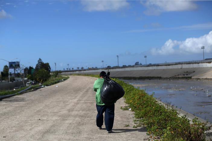 A Mexican who was recently deported from the U.S. carries a black bag next Tijuana river, in Tijuana, Mexico, February 22, 2017. REUTERS/Edgard Garrido