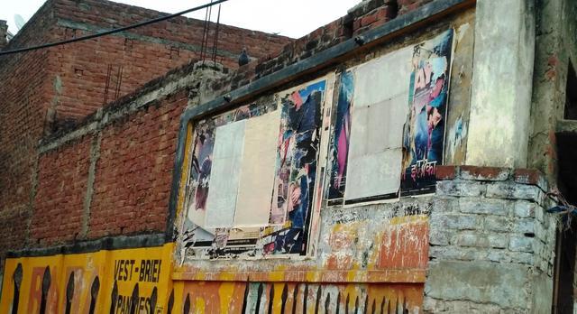 Torn film posters at Milan Talkies. Photo by Zeyad Khan