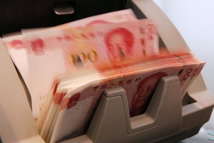 2016年3月,北京一家银行雇员使用点钞机清点人民币纸币。REUTERS/Kim Kyung-Hoon