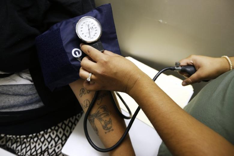 Janis Herrera, 25, gets her blood pressure measured on the first day of the new Pueblo del Rio Housing Projects Wellness Center, a free clinic that will serve 3,500 low income residents, in Los Angeles, California August 7, 2014. REUTERS/Lucy Nicholson