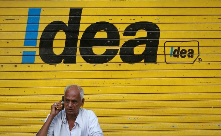 FILE PHOTO: A man speaks on his mobile phone as he sits in front of a shop displaying the Idea Cellular Ltd's logo on its shutter in Mumbai, India, April 28, 2014. REUTERS/Danish Siddiqui/File Photo
