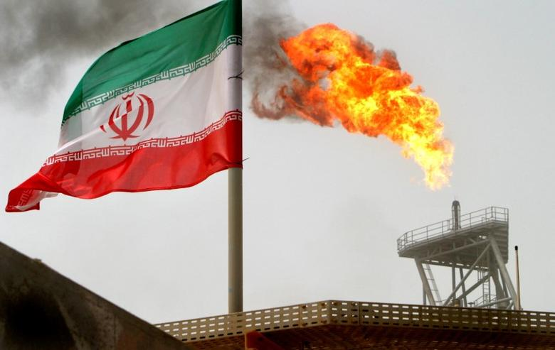 FILE PHOTO: A gas flare on an oil production platform in the Soroush oil fields is seen alongside an Iranian flag in the Persian Gulf, Iran July 25, 2005. REUTERS/Raheb Homavandi/File Photo