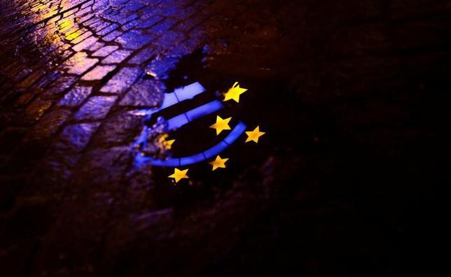 2月26日、今年のユーロ圏経済は、年初から成長の力強さを示す統計や調査結果が相次ぐが、景気が回復基調を維持できるかどうかはインフレと政治という「2大リスク」のすう勢に掛かっている。写真は水たまりに反射するユーロの彫刻。フランクフルトで2012年1月撮影(2017年 ロイター/Kai Pfaffenbach)