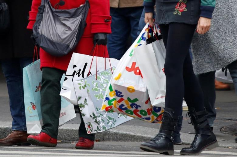 Shoppers carry shopping bags as they take care of their last-minute Christmas holiday gift purchases outside department stores in Paris, France, December 23, 2016.  REUTERS/Charles Platiau