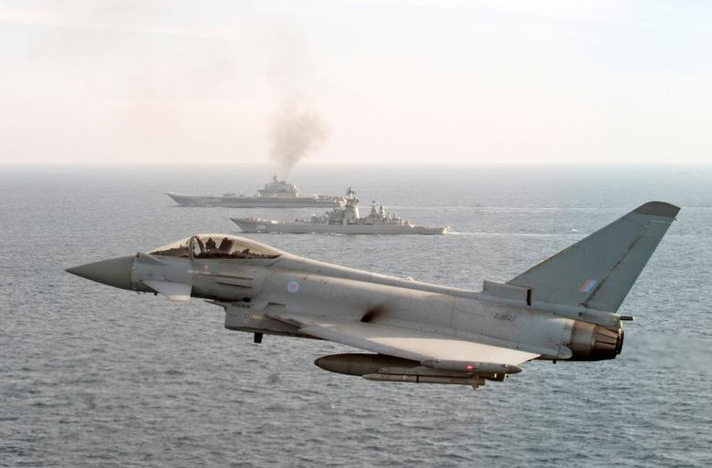 A RAF Typhoon monitors Russian warships Pyotr Velikiy and the Admiral Kuznetsov (rear) as they pass close to UK territorial waters, in this photograph released in London on January 25, 2017.  Ministry of Defence/Crown Copyright 2017/Handout via REUTERS