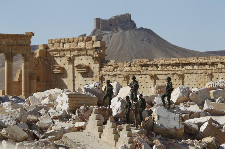 Syrian army soldiers stand on the ruins of the Temple of Bel in the historic city of Palmyra, in Homs Governorate, Syria April 1, 2016. REUTERS/Omar Sanadiki/Files