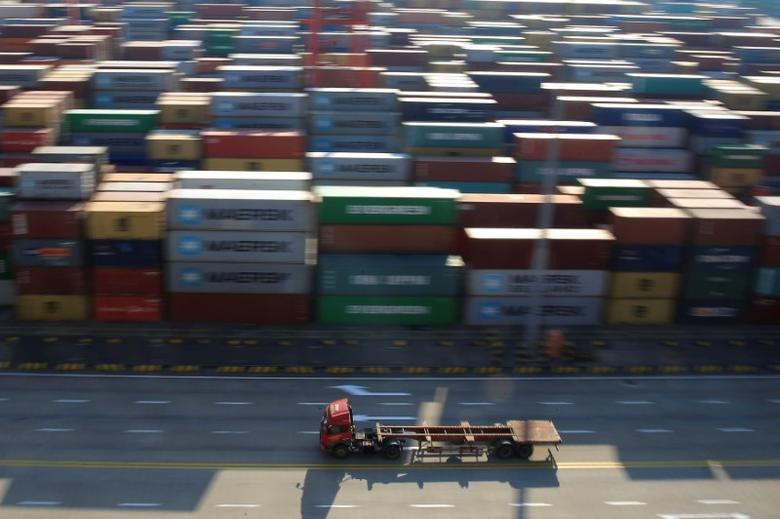 A truck drives past container boxes at the Yangshan Deep Water Port, part of the Shanghai Free Trade Zone, in Shanghai, China, February 13, 2017. REUTERS/Aly Song