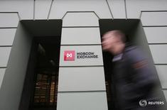 Мужчина проходит мимо здания Московской биржи  7 ноября 2014 года. Российские фондовые индексы не удержались в плюсе во второй половине сессии четверга, бумаги Аэрофлота теряют больше рынка, несмотря на отчет о прибыли за 2016 год. REUTERS/Maxim Shemetov