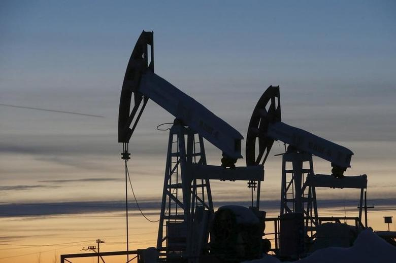 Pump jacks are seen at the Lukoil-owned Imilorskoye oil field, as the sun sets, outside the west Siberian city of Kogalym, Russia, in this January 25, 2016 file photo.  REUTERS/Sergei Karpukhin/Files
