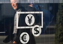 """Прохожие отражаются в витрине пункта обмена валюты в Токио 27 ноября 2014 года. Представители финансовых властей стран """"Большой двадцатки"""" вряд ли отойдут от обещаний бороться с валютными войнами на встрече в Германии в марте, несмотря на критику валютных курсов целого ряда государств клуба со стороны президента США Дональда Трампа, сказал бывший японский дипломат, отвечавший за финансовую политику. REUTERS/Issei Kato/File Photo"""
