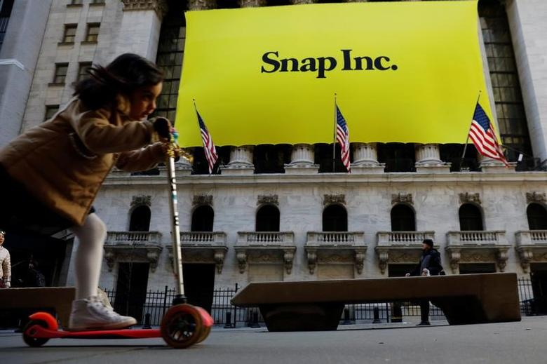 A young girl pushes her scooter past the front of the New York Stock Exchange (NYSE) with a Snap Inc. logo hung on the front of it shortly before the company's IPO in New York, U.S., March 2, 2017.  REUTERS/Lucas Jackson