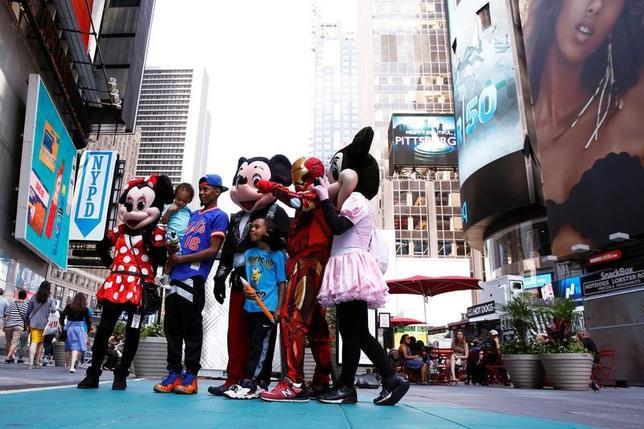 3月2日、米トランプ政権の排外主義的な姿勢が、米国の観光業に悪影響を及ぼしつつある。写真は、NY市のタイムズスクエアでコスチュームを着たキャラクターと写真を撮る観光客。昨年6月撮影(2017年 ロイター/Lucas Jackson)