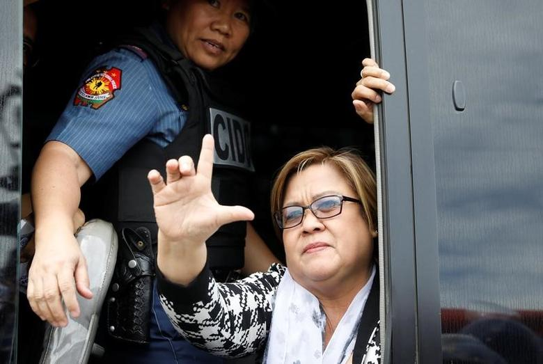 A policewoman guards Philippine Senator Leila De Lima as she gestures a sign that means ''Laban'' (Fight) sign after appearing at a court on drug related charges in Muntinlupa, Metro Manila, Philippines February 24, 2017.    REUTERS/Erik De Castro