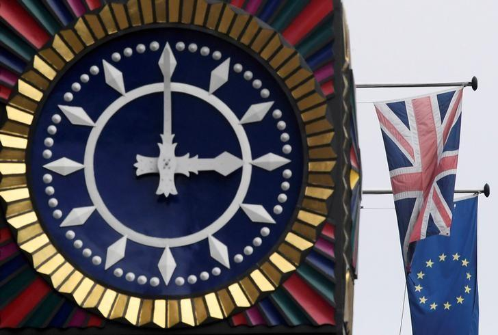 The British Union flag and the European Union flag are seen flying behind a clock in the City of London, Britain, January 16, 2017. REUTERS/Toby Melville/File Photo