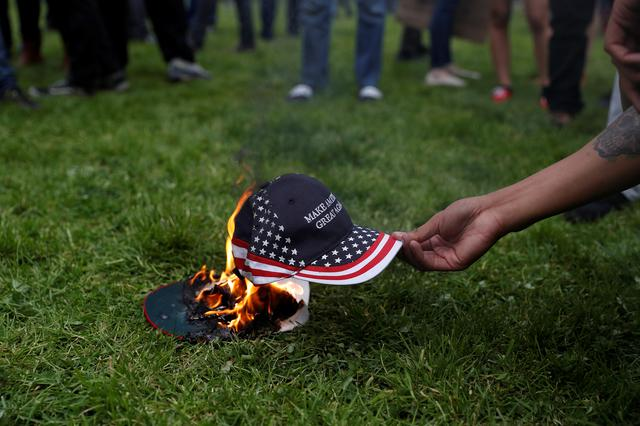 A demonstrator in opposition of President Trump sets a hat on fire during a ''People 4 Trump'' rally in Berkeley, California. REUTERS/Stephen Lam