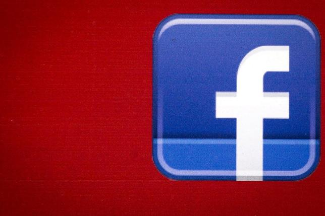 3月6日、米フェイスブックはイタリアでの位置情報共有機能「ニアバイ・プレーシズ」の提供を停止した。ミラノの裁判所が昨年8月、同社による競争法及び著作権法侵害を認めたことを受けたもの。写真のフェイスブックロゴは、ニューヨーク金融街を走るツアーバスのボディに描かれていたもの。2015年7月撮影(2017年 ロイター/Brendan McDermid)