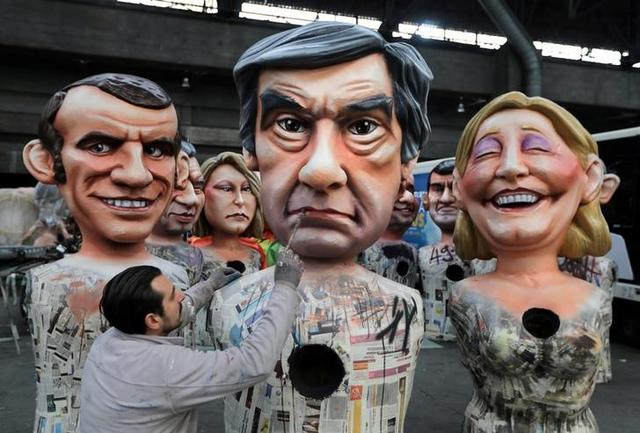 A worker puts the final touches to a giant figure of Francois Fillon (C), former French prime minister, member of The Republicans political party and 2017 presidential candidate of the French centre-right, next to French National Front leader Marine Le Pen (R) and Emmanuel Macron (L), head of the political movement En Marche !, or Onwards !, during preparations for the carnival parade in Nice, France, February 2, 2017.   REUTERS/Eric Gaillard
