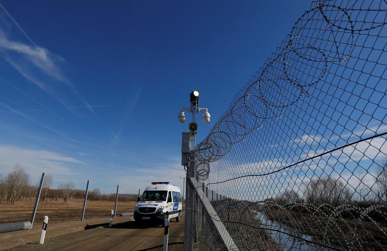 A Hungarian police van passes by an intelligent fence post as it patrols the fortified Hungary-Serbia border near the village of Asotthalom, Hungary March 2, 2017. REUTERS/Laszlo Balogh
